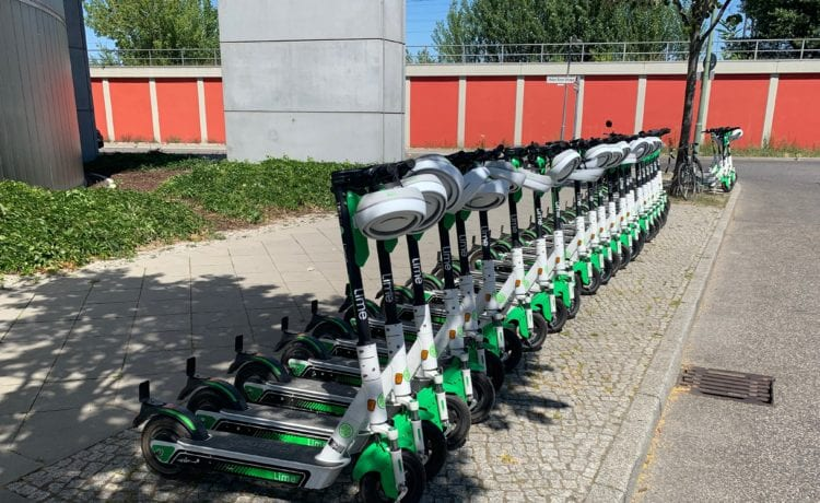Lime-E-Scooter aufgereiht und mit Helm. Foto: Matthias Bannert / MOViNC