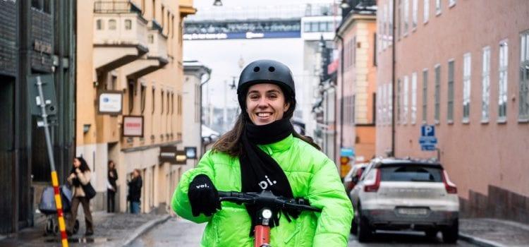 Eine Frau in Winterjacke fährt auf einem E-Scooter des Anbieters Voi auf einer Straße. Credit: Voi